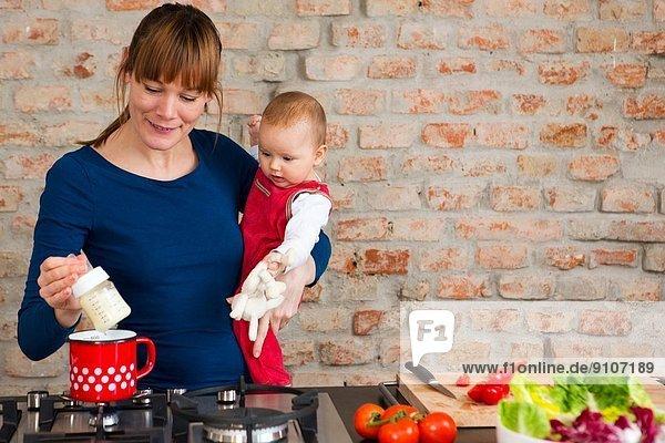 Mutter mit Tochter beim Zubereiten des Mittagessens