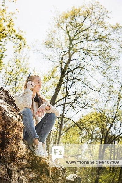 Junge Frau beim Chatten auf dem Smartphone im Wald
