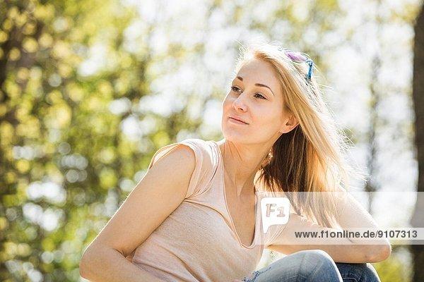 Porträt einer jungen Frau  die ruhig in den Wald blickt.