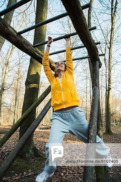 Junge Frau auf dem Klettergerüst im Wald auf dem Übungsgelände