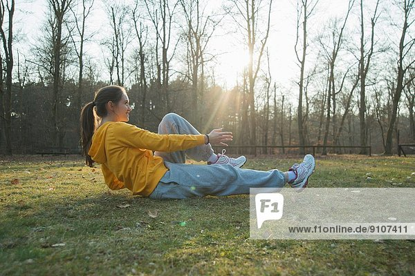 Junge Läuferin beim Aufwärmen Sit-ups