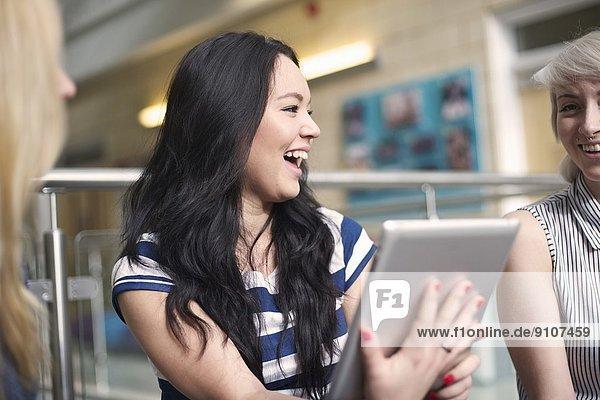 Junge Frau mit digitalem Tablett  lachend