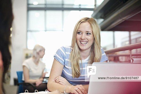 Junge Frau mit Laptop in der Bibliothek