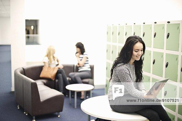 Junge Frau auf dem Tisch sitzend mit digitalem Tablett