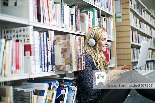 Junge Frau sitzt auf dem Boden in der Bibliothek mit Laptop