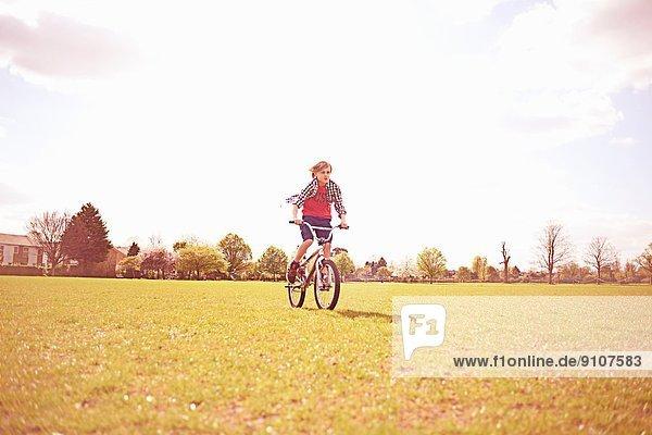Junge Radfahren auf dem Spielfeld
