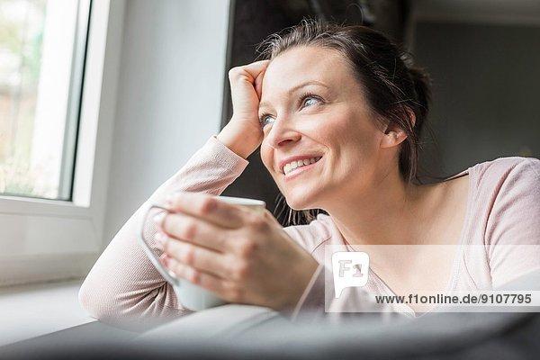 Mittlere erwachsene Frau mit Blick aus dem Fenster mit Kaffee