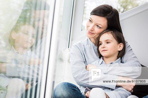 Mutter und Tochter umarmen sich am Fenster