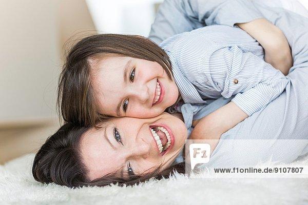 Mutter und Tochter auf dem Teppich liegend  lachend