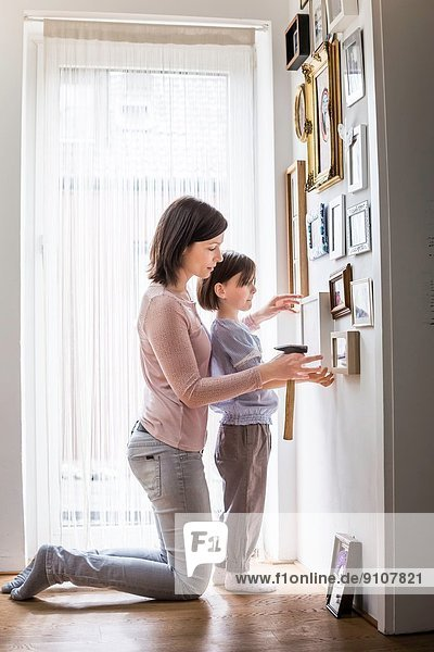 Mutter und Tochter hängen Bild an der Wand