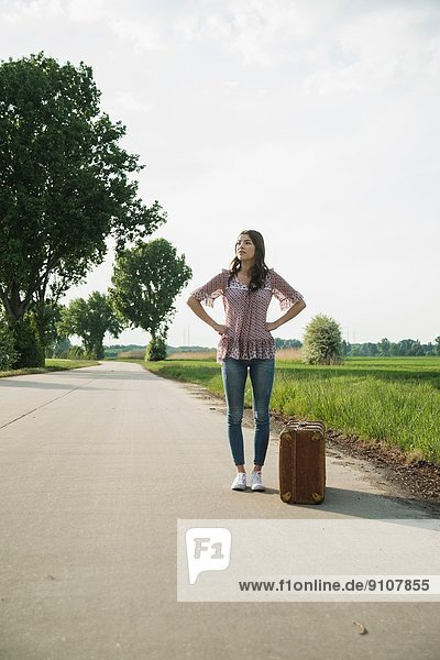 Young woman standing on country road with suitcase