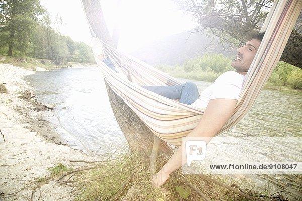 Junger Mann in der Hängematte am Fluss Toce  Piemonte  Italien