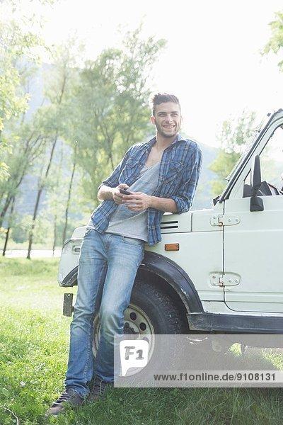 Junger Mann lehnt gegen Geländewagen
