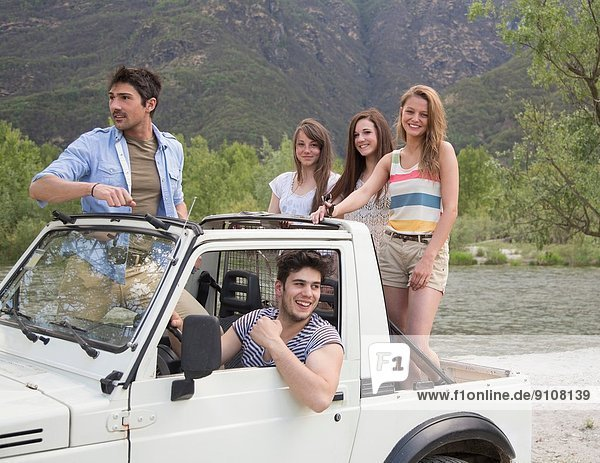 Freunde stehen auf dem Rücksitz des Geländewagens
