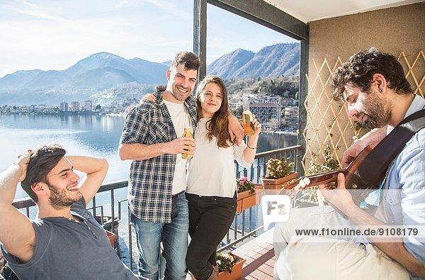 Vier Freunde auf dem Balkon  mit Gitarre und Bier