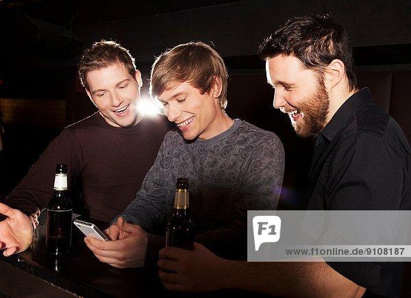 Three male friends looking at smartphone in nightclub