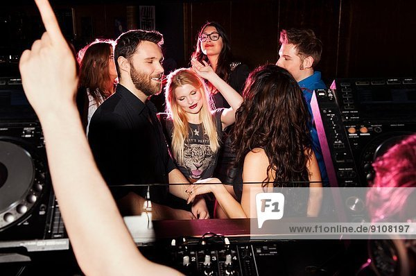 Gruppe junger Männer und Frauen  die vor dem DJ im Nachtclub tanzen.