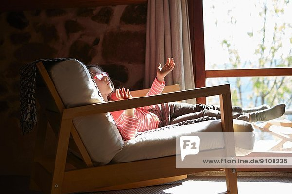 Young girl sitting on rocking chair daydreaming