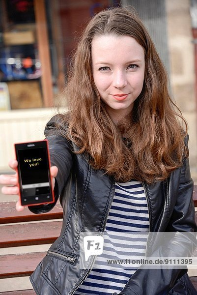Teen age girl showing a text message on her mobile.