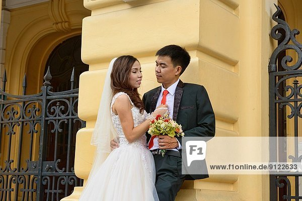 happy newlyweds in front of the Opera House in Hanoi  Vietnam.