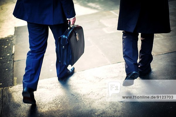 Two unrecognizable businessmen with portfolio walking down the street in the city of London  England  UK