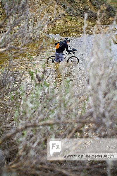 A man pushes his mountain bike through spring run off conditions on the Maah Daah Hey Trail  North Dakota