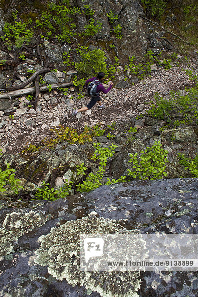 A young asian woman trail running in the 3 Blind Mice trail system. Penticton  BC
