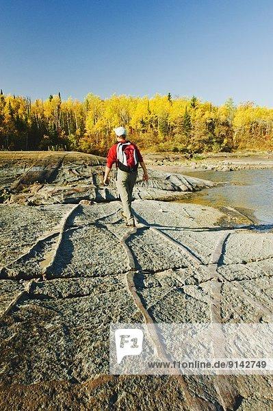 Hiking on precambrian shield rock along the Winnipeg River  near Seven Sisters  Manitoba  Canada