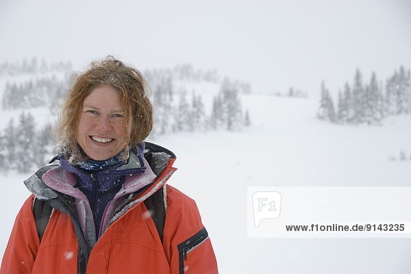 Woman smiling in snowy mountains  Canmore  Alberta  Canada