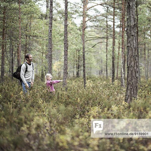 Mädchen zeigt Vater etwas im Wald