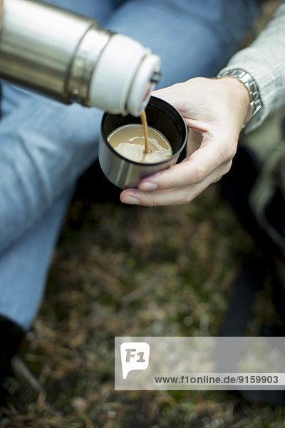 Abgeschnittenes Bild eines Mannes  der eine Tasse Kaffee ins Freie gießt.