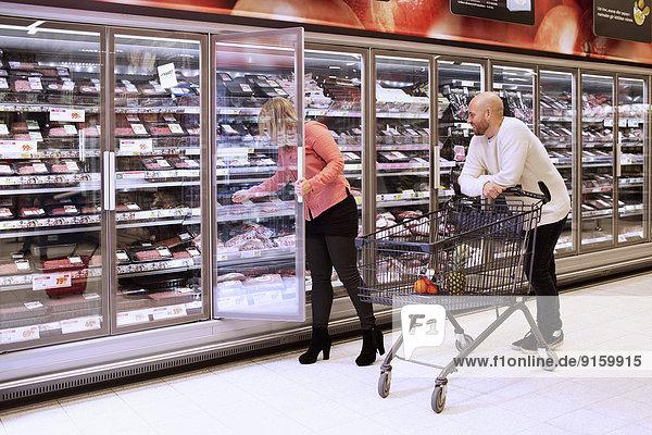 Mittleres erwachsenes Paar beim Einkaufen im Supermarkt