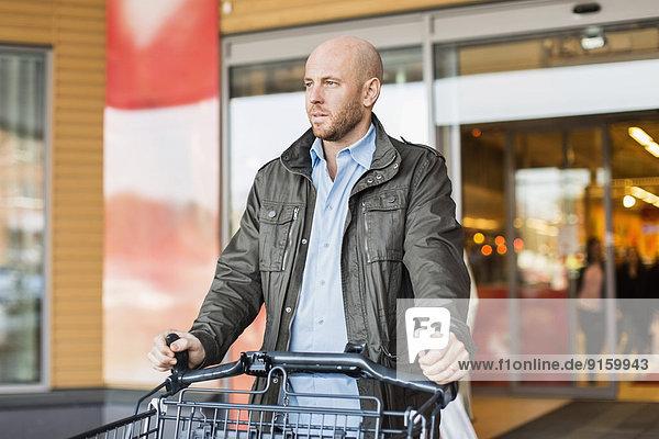 Mittlerer erwachsener Mann mit Einkaufswagen vor dem Supermarkt