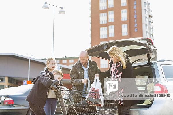 Familienverladung von Lebensmitteln im Kofferraum auf dem Parkplatz