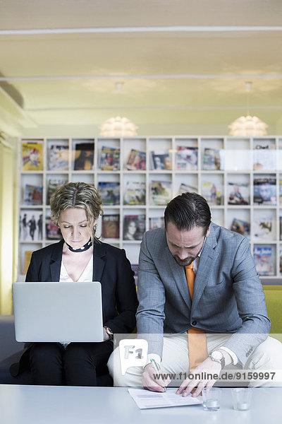 Reife Geschäftsfrau mit Laptop und Kollegin beim Unterschreiben von Dokumenten im Kreativbüro