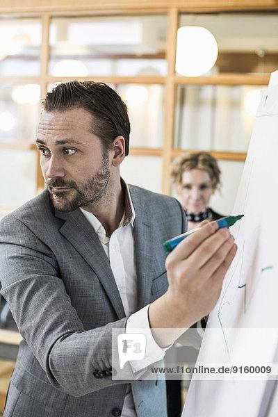 Mittlerer Erwachsener Geschäftsmann beim Schreiben auf Flipchart mit Kollegin im Hintergrund im Büro