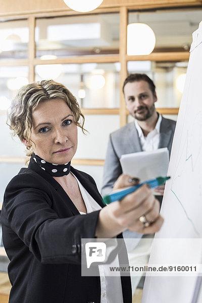 Porträt einer reifen Geschäftsfrau auf Flipchart mit männlichem Kollegen im Hintergrund im Büro