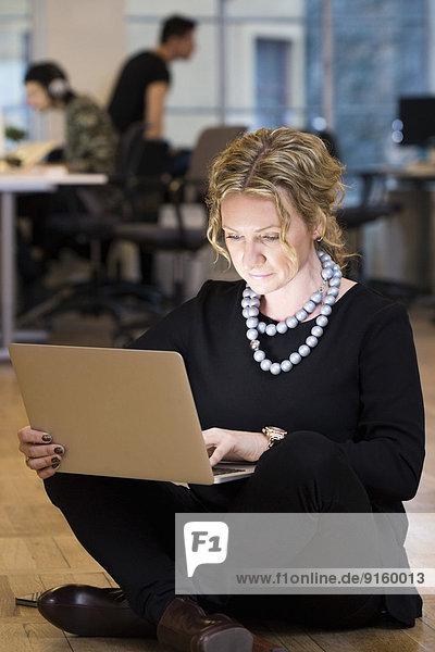 Volle Länge der reifen Geschäftsfrau mit Laptop  während sie im Büro auf dem Boden sitzt.