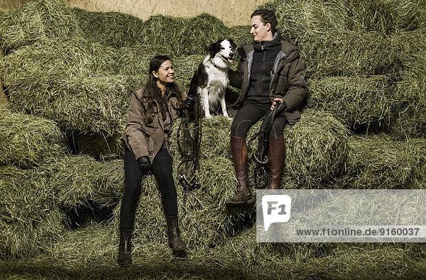 Durchgehende Rückansicht des glücklichen jungen Paares mit Hund auf dem Heuhaufen im Stall