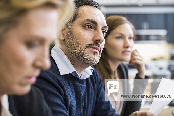 Konzentrierter Geschäftsmann schaut weg in Bürobesprechung