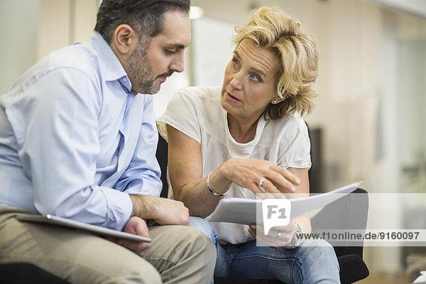 Geschäftsleute mit Dokumentenplanungsstrategie im Büromeeting