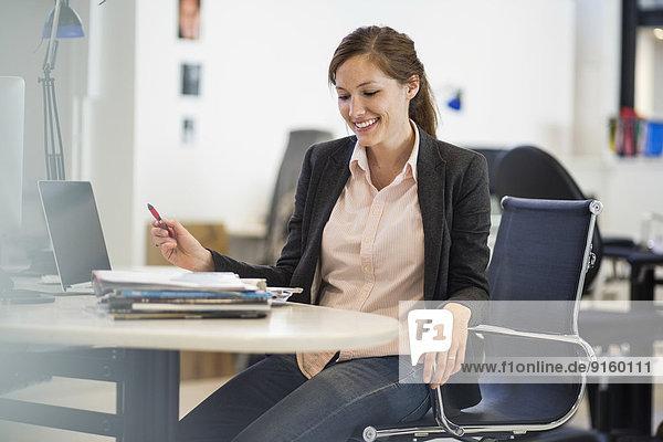 Lächelnde Geschäftsfrau am Schreibtisch im Büro