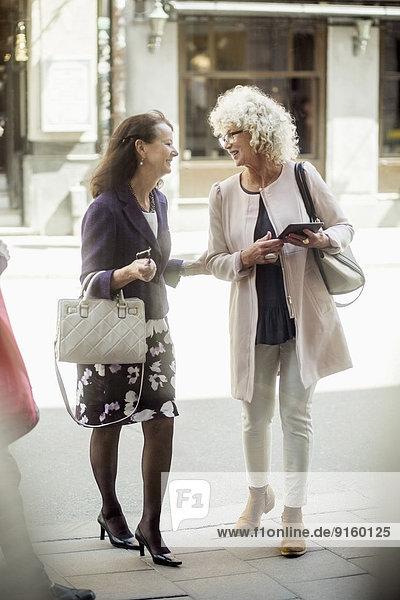 Fröhliche ältere Freundinnen  die beim Spazierengehen auf der Straße reden