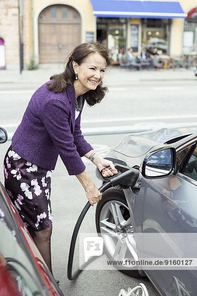 Lächelnde Seniorin tankt Auto auf der Straße