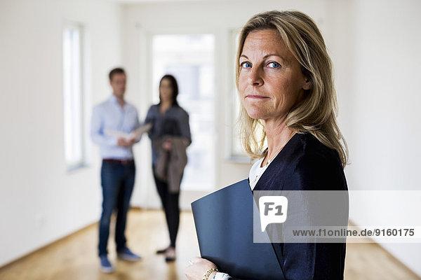 Porträt einer selbstbewussten Immobilienmaklerin mit einem im Hintergrund stehenden Paar zu Hause