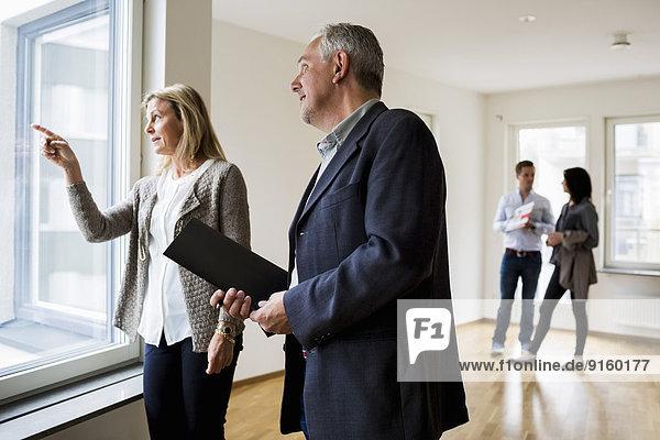 Immobilienmakler diskutieren  während ein Paar im Hintergrund bei einem neuen Zuhause steht
