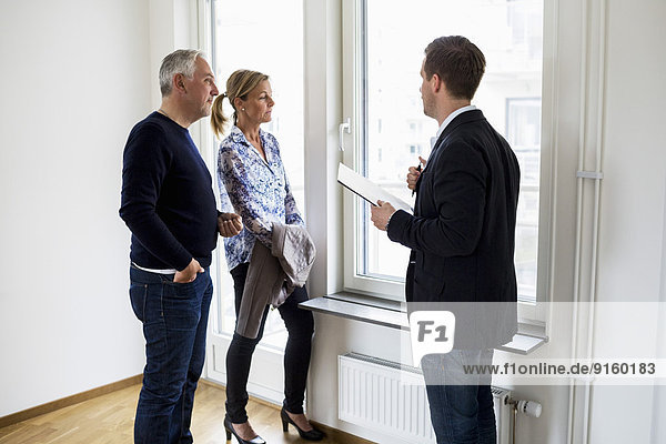 Männlicher Immobilienmakler im Gespräch mit dem Paar zu Hause