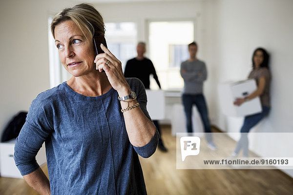 Reife Frau  die das Handy benutzt  während die Familie zu Hause Umzugskartons im Hintergrund trägt.