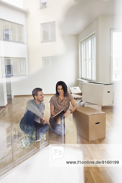 Full length of couple reading brochure into their new house