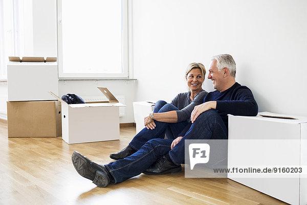 Reife Paare entspannen sich nach dem Einzug in ihr neues Haus